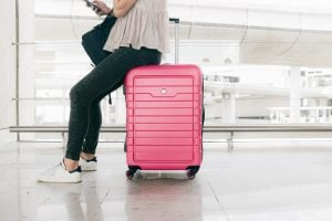 woman sitting on a pink suitcases