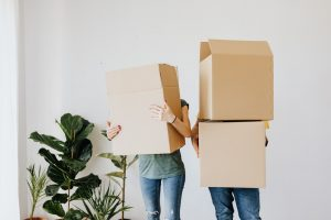 two people holding cardboard boxes
