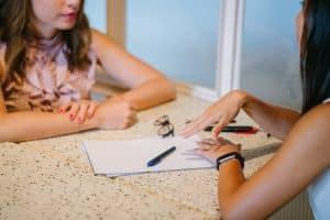 two women sitting, talking, business