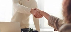 A mover and a woman shaking hands before she decides to move antique furniture with his help