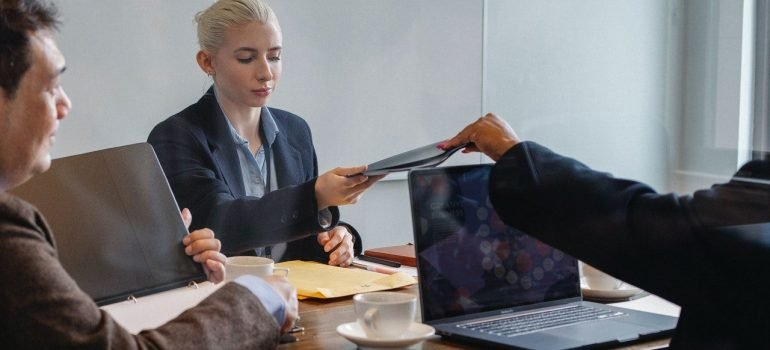 a man handing a file to a woman across the desk