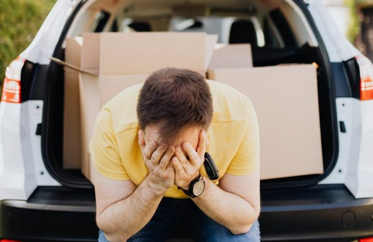 A man sitting at the back of his car, loaded with moving boxes.