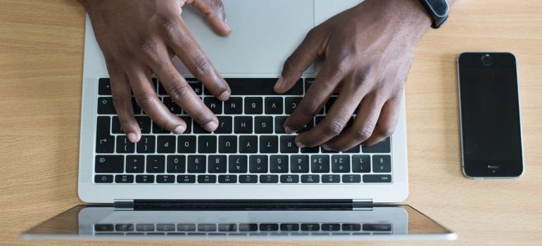 Human hands typing on the keyboard of a laptop, which is on the desk