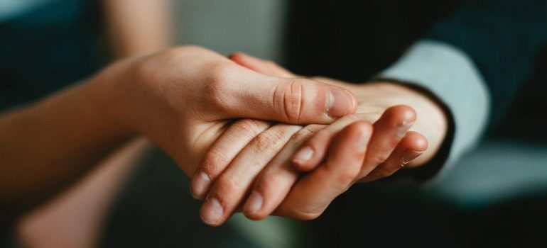 Hand holding another hand in terms of assisting while moving a business overseas