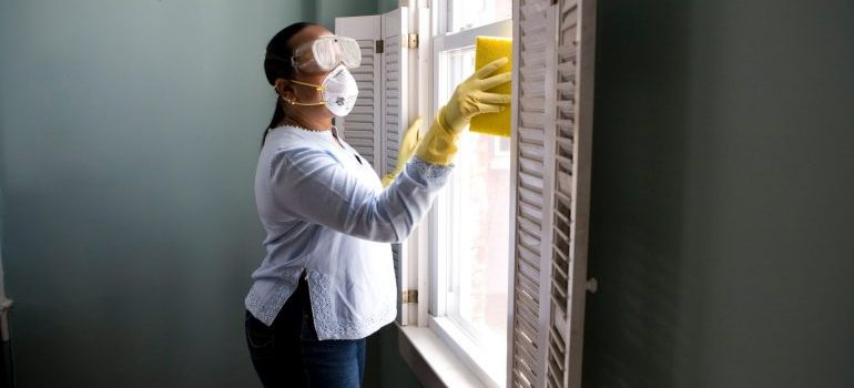 A woman cleaning windows with all equipment needed for spring cleaning before and after moving