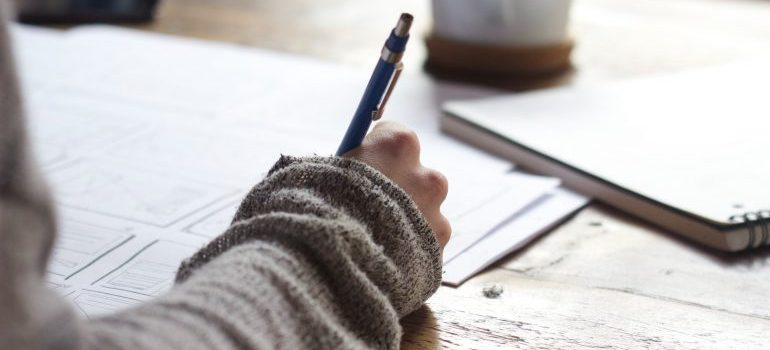 A human hand holding a pencil, writing on the paper