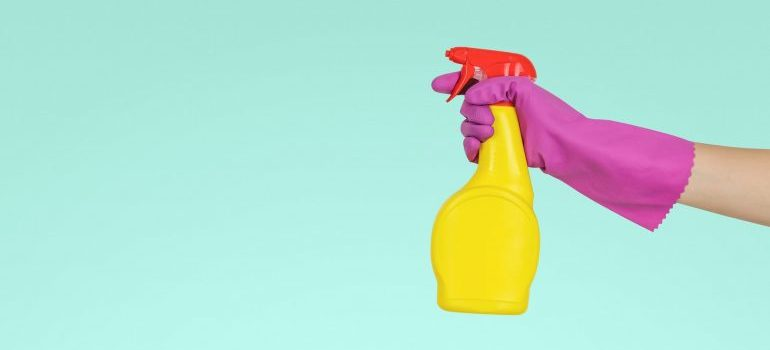 A hand with a glove in hand holds a cleaning spray
