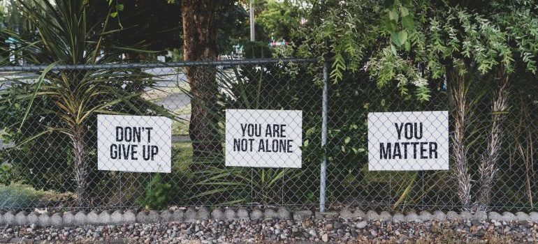Three quotes are written on paper, hanging on a fence
