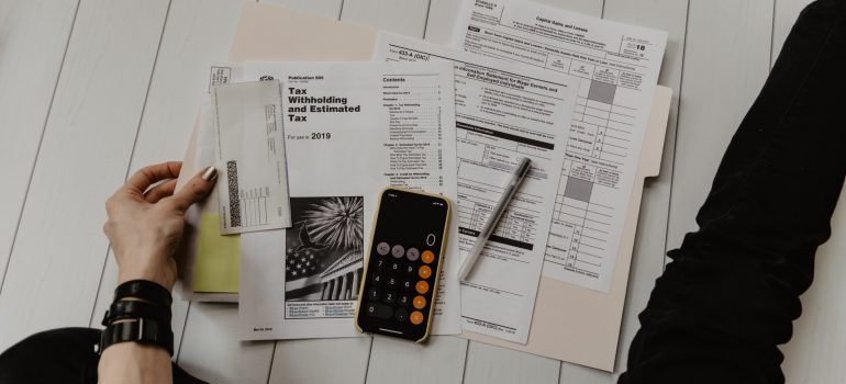 A person calculating their budget on the paper