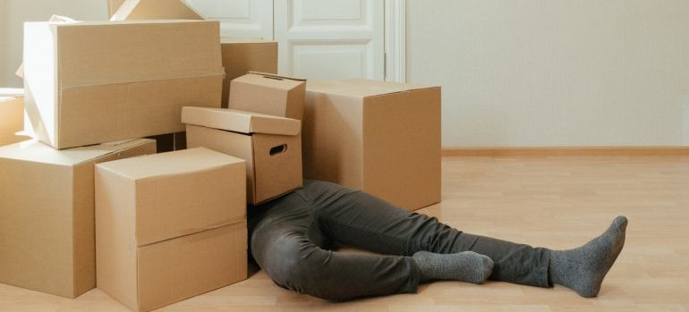 man laying on the floor with a bunch of boxes on top of him