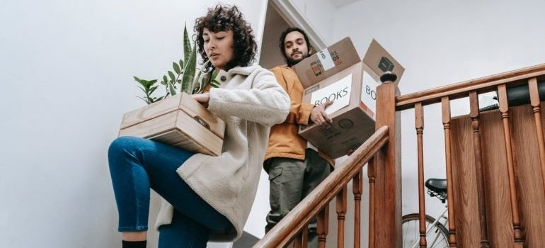 man and woman on the stairs carrying full boxes