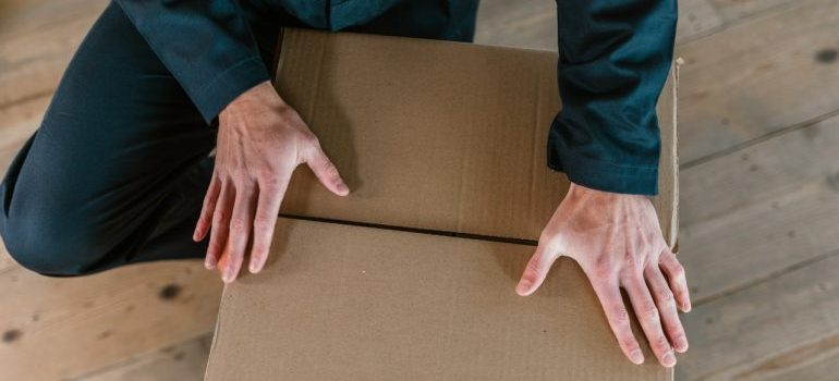 man in dark green jumpsuit holding his hands on the paper box