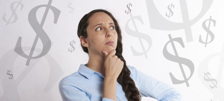 woman in a thinking pose with dollar signs floating behind her