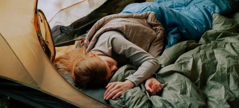 Woman sleeping in a camping sleeping bag