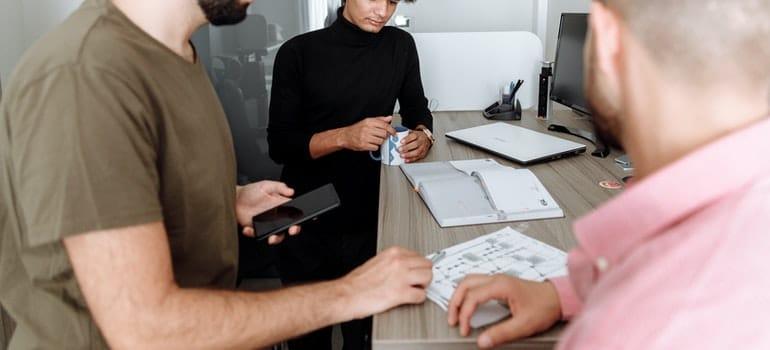 Men planning laboratory equipment relocation.