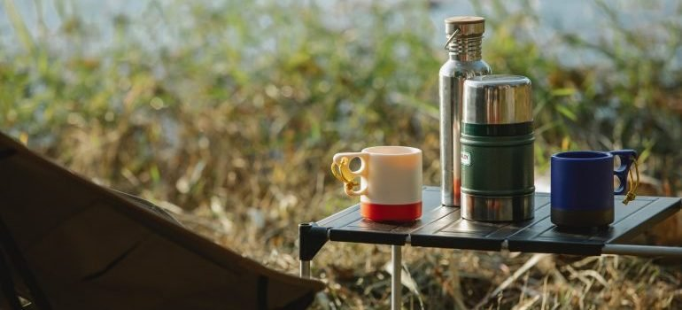 Camping mugs and thermos on a table