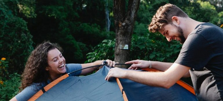 Man and woman preparing tent for packing and moving