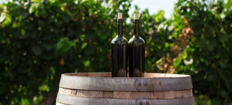 Two wine bottles on a barrel, is a field