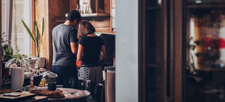 After choosing the best time to buy a house in Fort Lauderdale, a couple is in the kitchen of their home, preparing a meal.