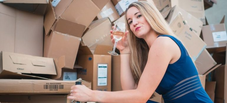 After moving your wine collection in North Miami, a woman is posing in front of boxes with a wine glass in her hands.