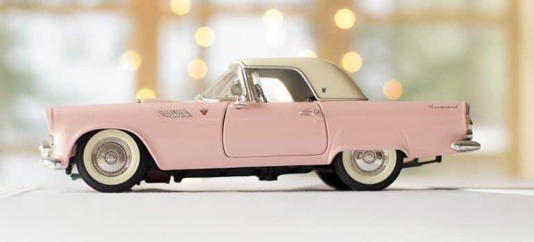 A pink model of an antique car.