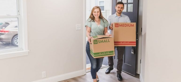 Woman and man carrying boxes